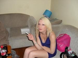 blonde sexy fume dans le salon
