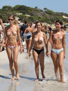 des femmes se promènent seins nus à la plage