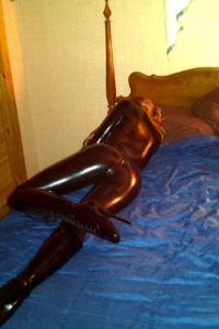 femme couchée sur le lit en combinaison intégrale latex